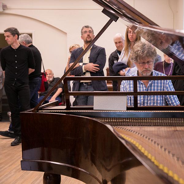 Xak Bjerken playing the piano in reception